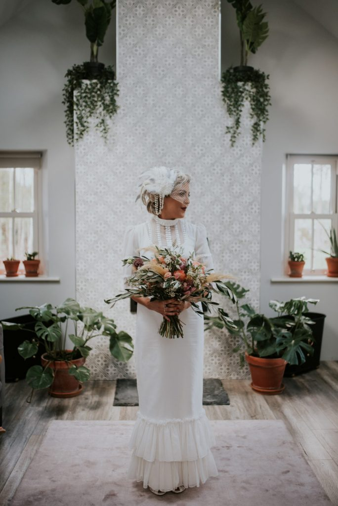 The bride was wearing a vintage-inspired wedding dress with a high neckling, short sleeves and a ruffle skirt plus ruffles