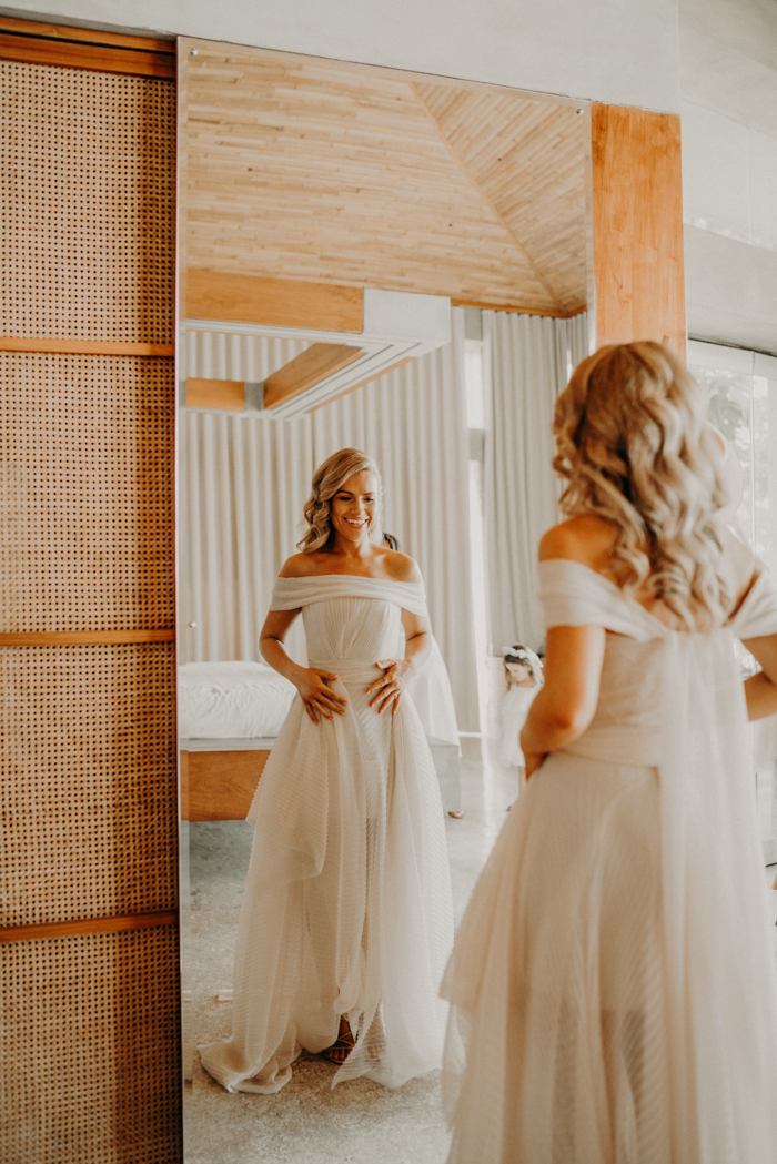 Her layered off the shoulder wedding dress with an asymmetric skirt was designed and made by herself