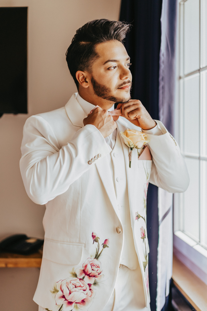 One groom was wearing a white three-piece wedding suit with hand painted flowers