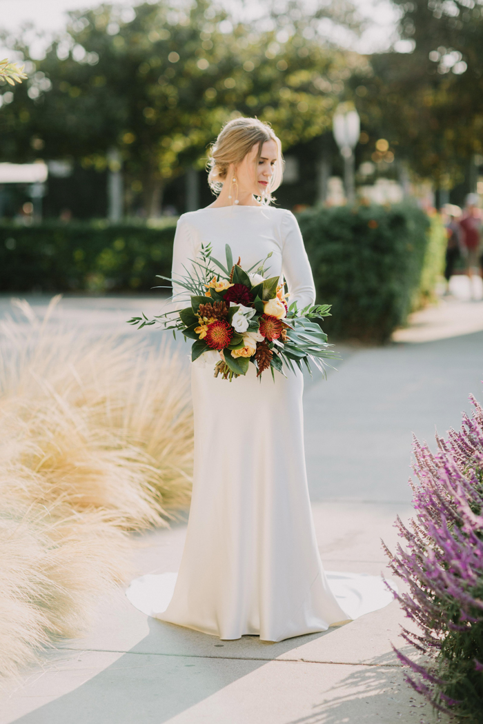 The bride was wearing a minimalist plain wedding dress with long sleeves