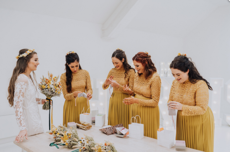 The bridesmaids were wearing yellow matching dresses with lace bodices and pleated skirts