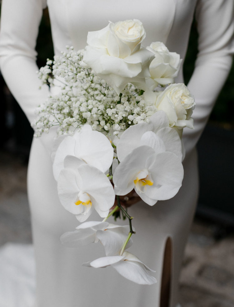 The wedding bouquet was done with white roses, orchids and baby's breath