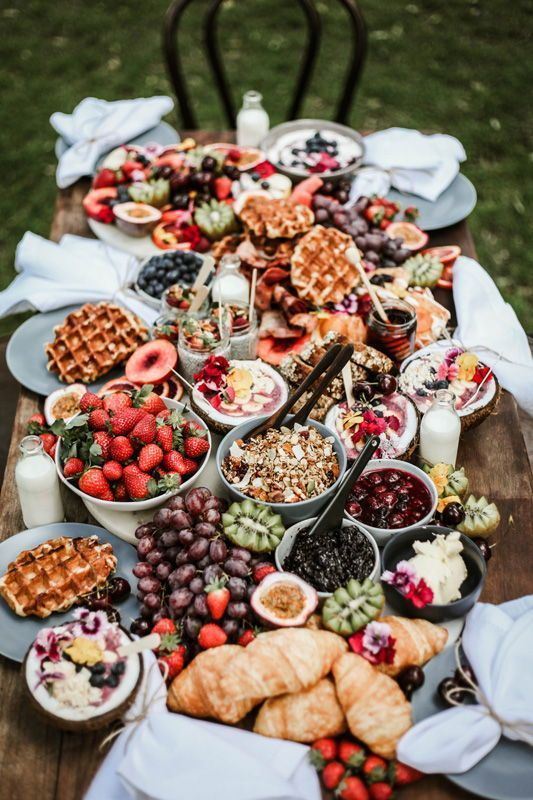 a lush waffle and fruit grazing table with milk, dips, sauces, berries and tropical blooms is just wow