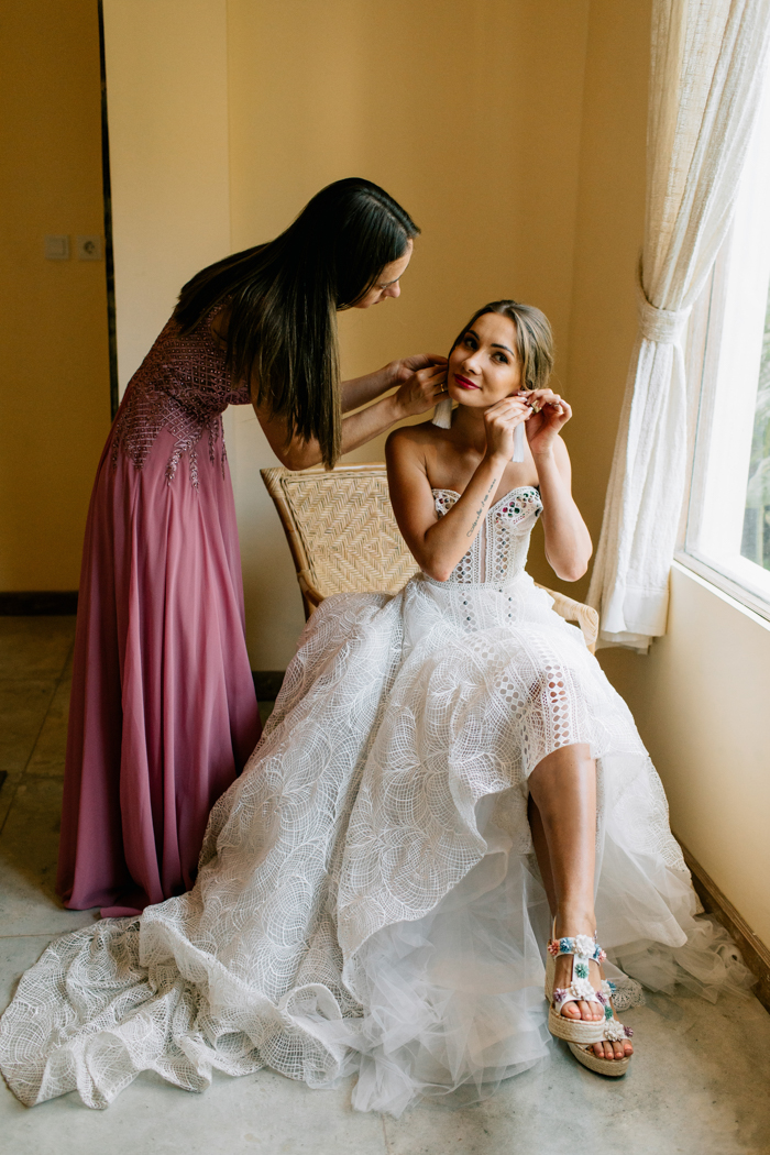 The bride was wearing a boho lace strapless A-line wedding dress with colorful crystals lining up the bodice and bright platform shoes, she finished the look with tassel earrings