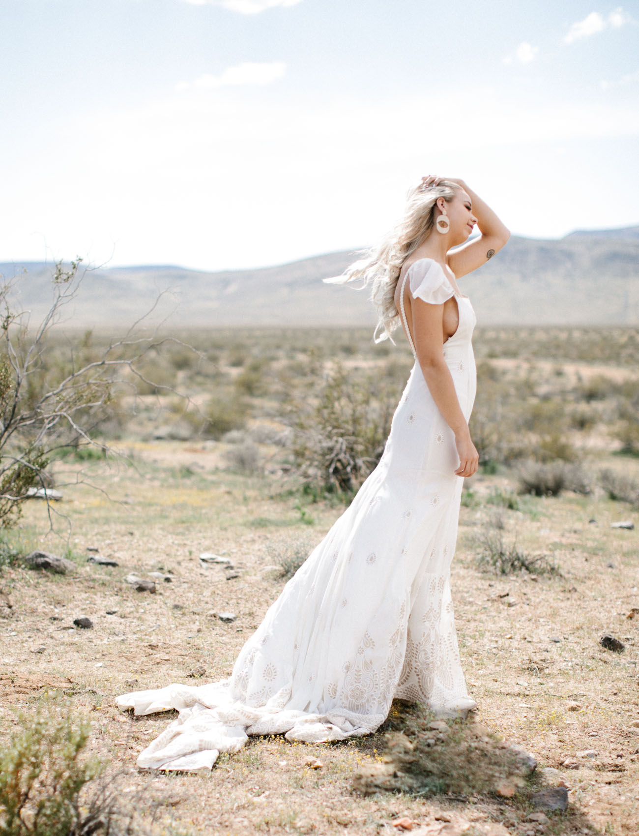 The bride was wearing an A line wedding dress with a square cut, ruffle cap sleeves and tan boho lace
