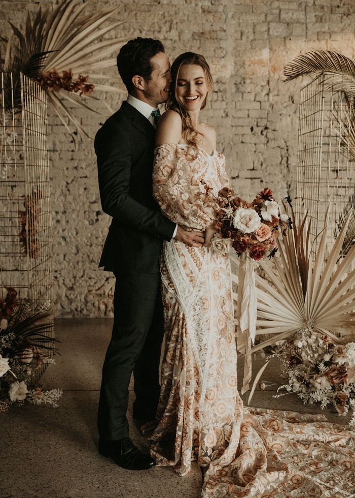 The bride was wearing an off the shoulder wedding dress with floral appliques, puff sleeves and a train