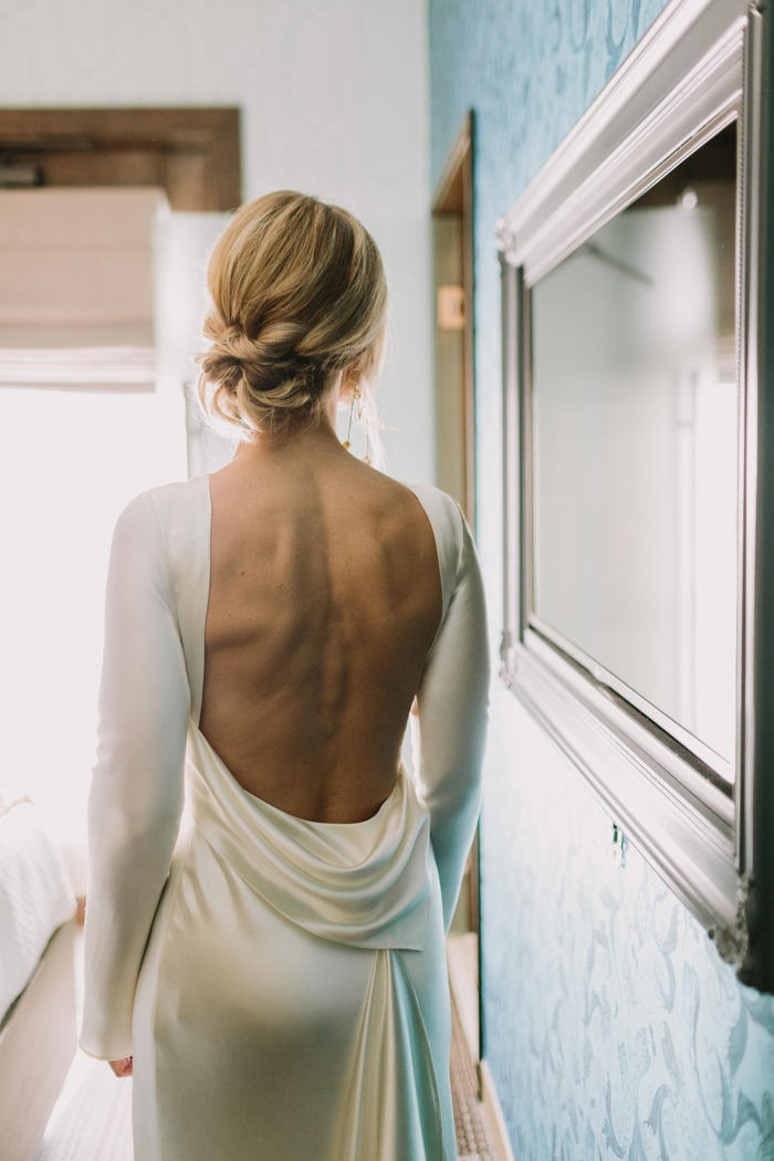 The dress features an open back and the bride also rocked a twisted low updo
