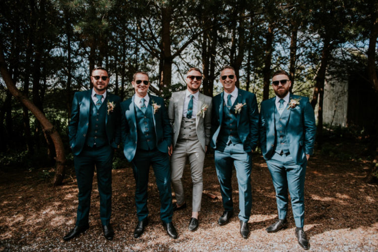 The groom was wearing a plaid three-piece suit, a blue tie and moccasins, the groomsmen were rocking navy three-piece suits