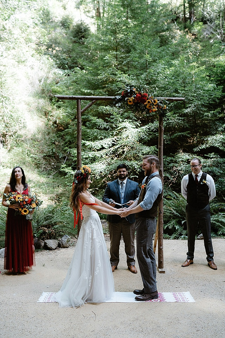The wedding arch was decorated with greenery and bright blooms, the bridesmaids were wearign burgundy dresses