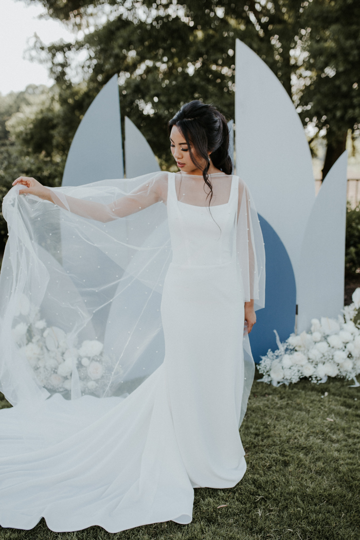 The bride was wearing a minimalist sheath wedding dress with thick straps and a pearl capelet