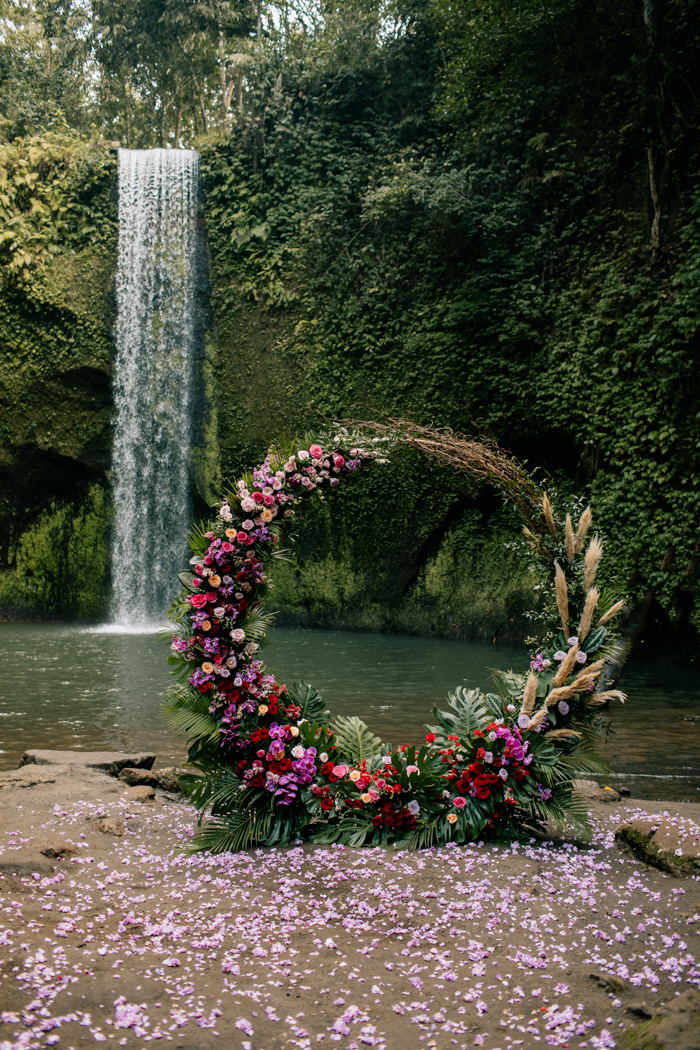 The wedding arch was a round one, decorated with tropical leaves and super bold blooms in various colors