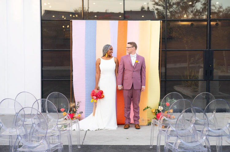 The wedding ceremony space was done with a bright striped backdrop, bright florals and sheer chairs