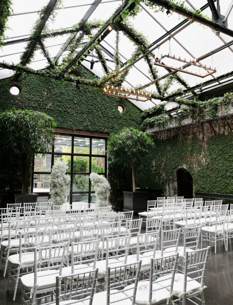 The wedding ceremony space was done with lots of greenery, chandeliers, a baby's breath altar and white chairs