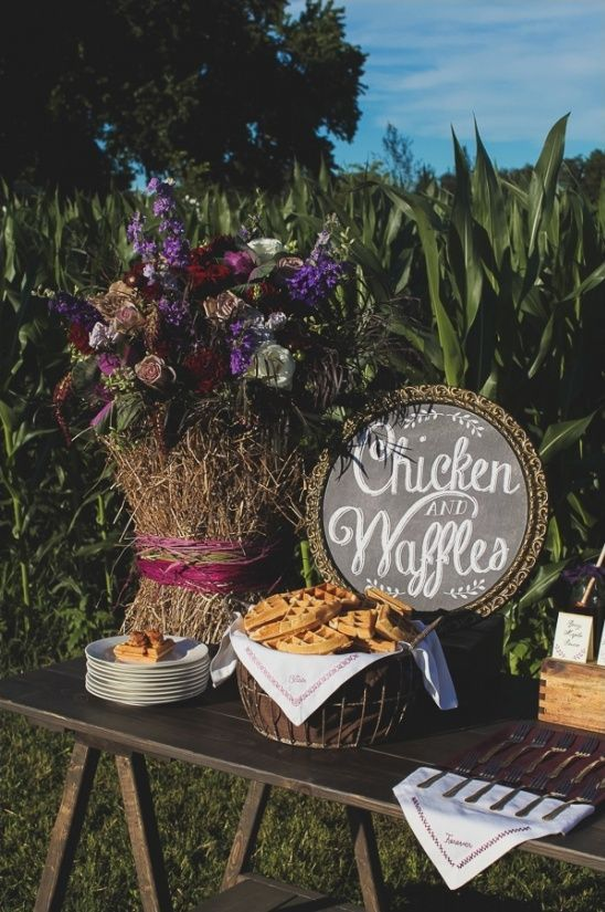 a rustic chicken and waffle bar with a chalkboard sign, bright blooms, lots of waffles and chicken served