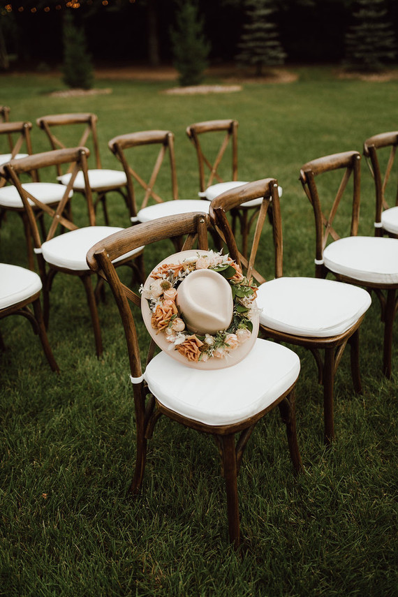 The bride was rocking a cream hat decorated with rust and blush blooms and greenery