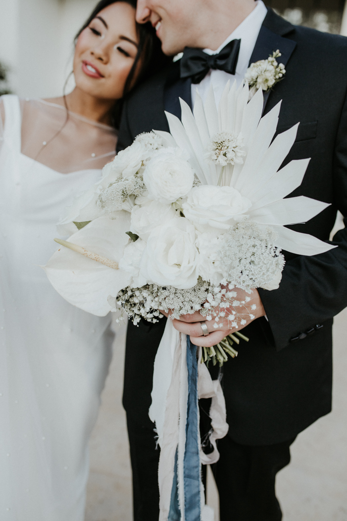 The wedding bouquet was all-white, with beautiful blooms and dried fronds