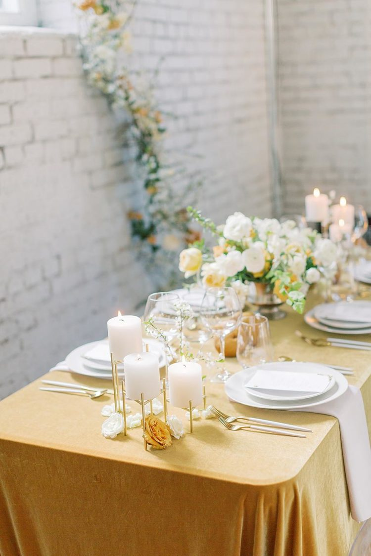 The wedding table setting was done with mustard linens, neutral and mustard blooms and pillar candles