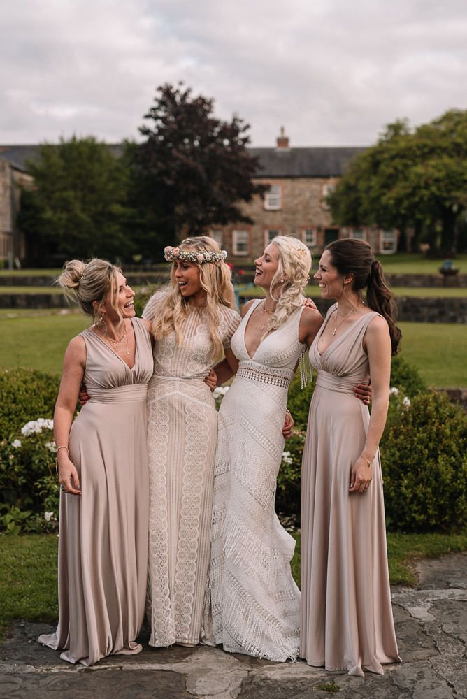 The bridesmaids were wearing champagne-colored draped maxi dresses with depe necklines