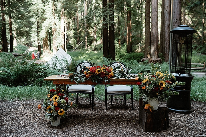 The wedding sweetheart table was done with bright blooms and greenery and with a heater next to it