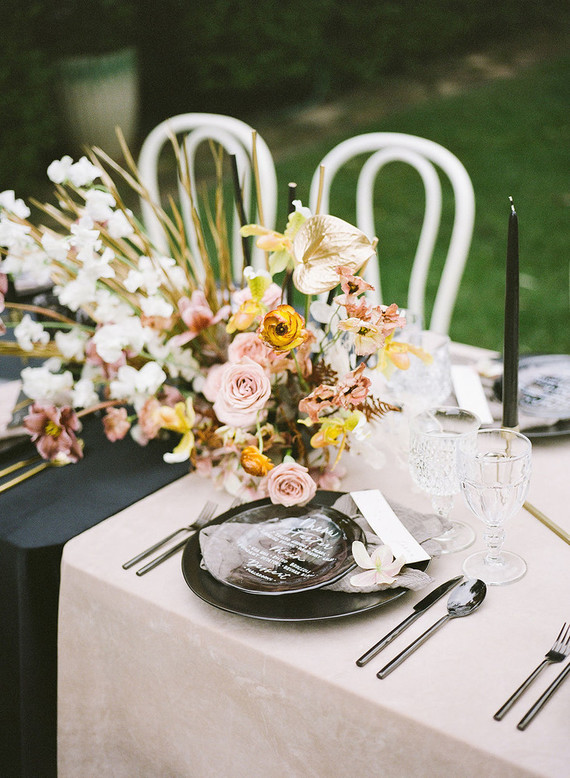 The wedding tablescape was done in blush and black, with black plates, chic menus, bold and lush blooms