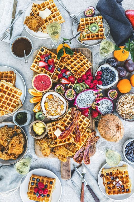 a simple wedding waffle grazing table with waffles, berries, tropical fruits, toppings and sauces