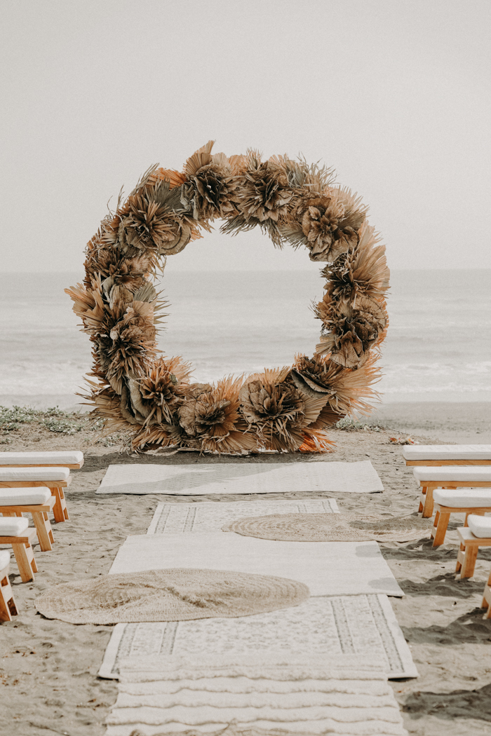 The wedding arch was round, made of fronds and dried leaves and looked very boho-like