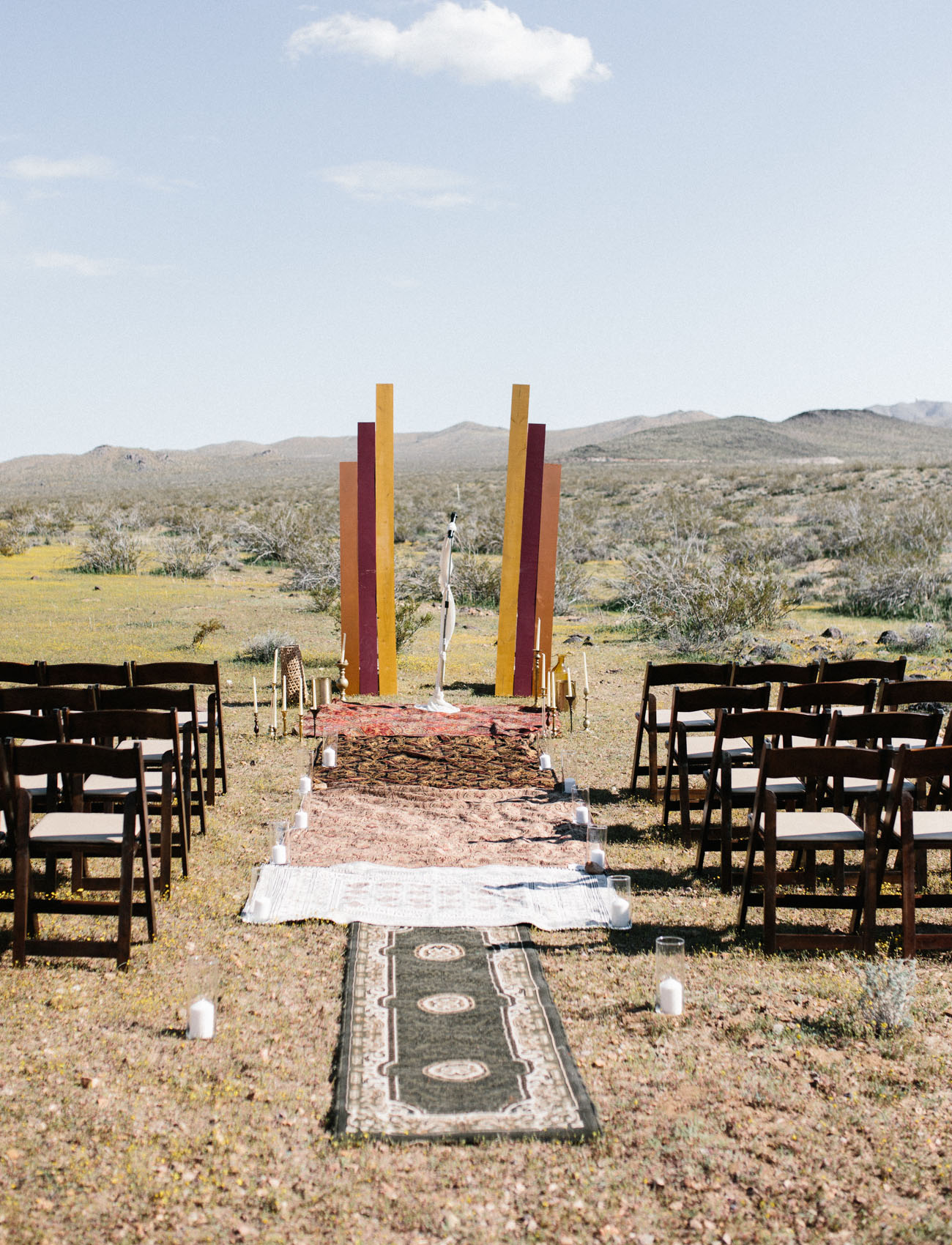 The wedding ceremony space was done with layered rugs, candles and colorful decor plus candlesticks