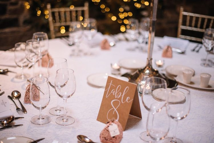 The wedding tablescapes were done with white lace linens, card table numbers and chic glasses