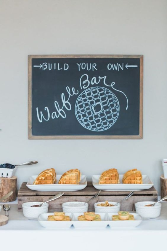a small waffle bar with a chalkboard sign, waffles, berries and fruits, toppings and syrups is simple and awesome