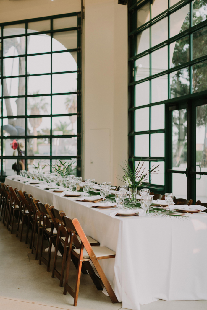 The wedding reception was decorated elegantly with tropical leaves and white blooms and white linens