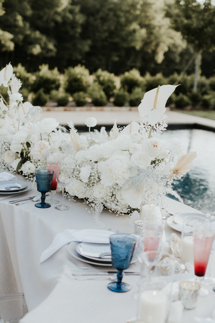 The wedding table was curved, with lush white blooms and blue glasses