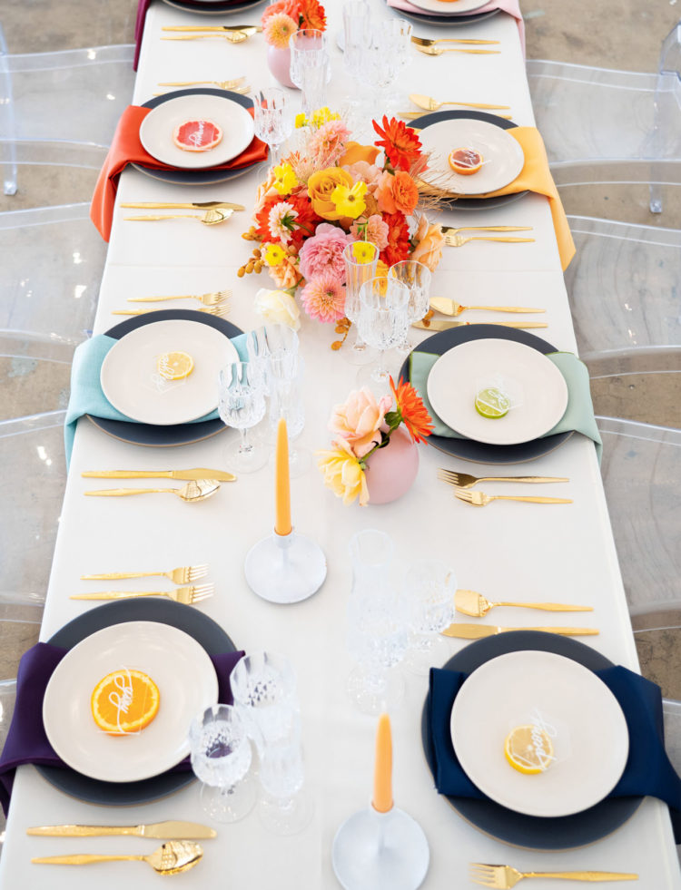 The wedding tablescape was done with bright florals, matte chargers, colorful napkins and citrus cards