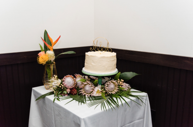 The wedding cake was a white one with a wire topper and served on king proteas