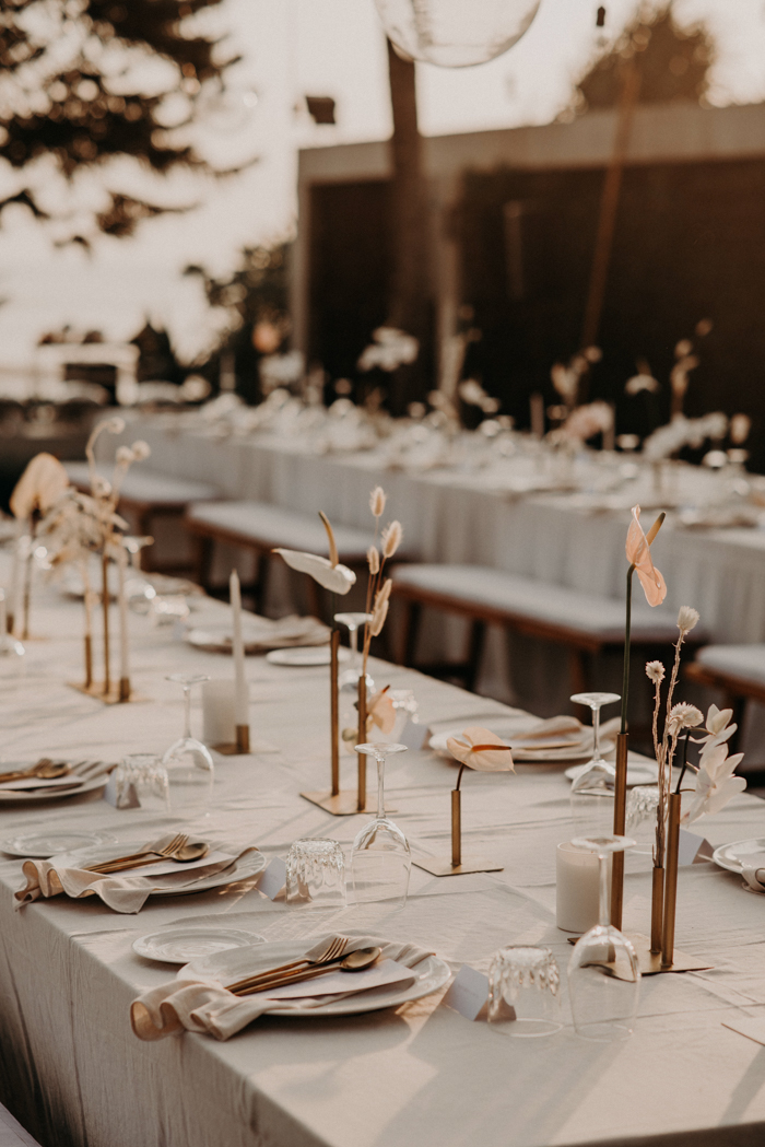 The wedding tablescapes were done with neutral linens, brass vases, candlesticks and cutlery