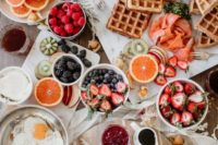 11 a waffle bar with fruits, berries, dips, honey, fried eggs and some wildflowers is ideal for a brunch wedding