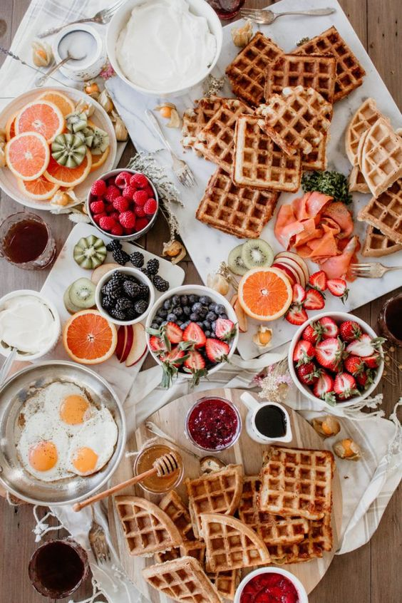 a waffle bar with fruits, berries, dips, honey, fried eggs and some wildflowers is ideal for a brunch wedding
