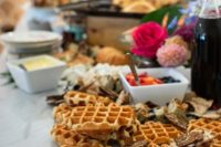 12 a stylish waffle bar with bright blooms, tropical leaves, waffles, toppings and sauces of all kinds
