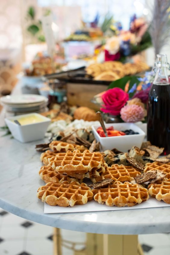 a stylish waffle bar with bright blooms, tropical leaves, waffles, toppings and sauces of all kinds