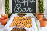 13 a waffle bar with toppings in terra cotta pots, a chalkboard sign covered with a greenery garland