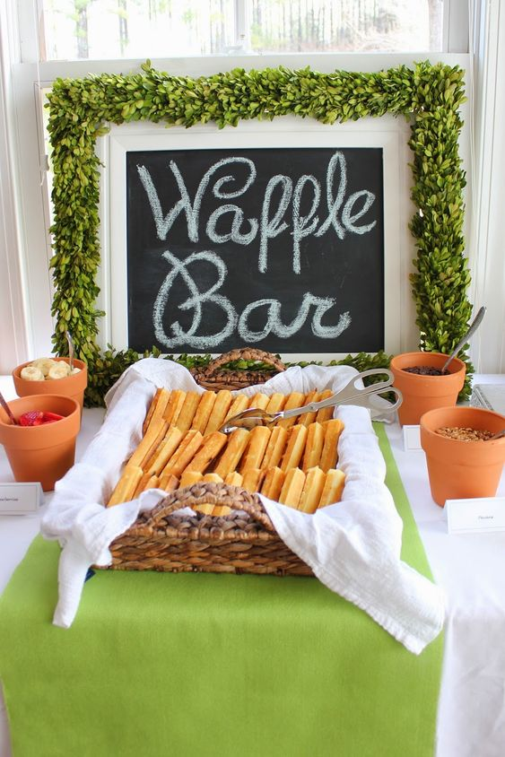a waffle bar with toppings in terra cotta pots, a chalkboard sign covered with a greenery garland