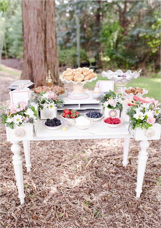 an elegant vintage waffle bar with a white vintage table, pink and white blooms, greenery, waffles, toppings and sauces