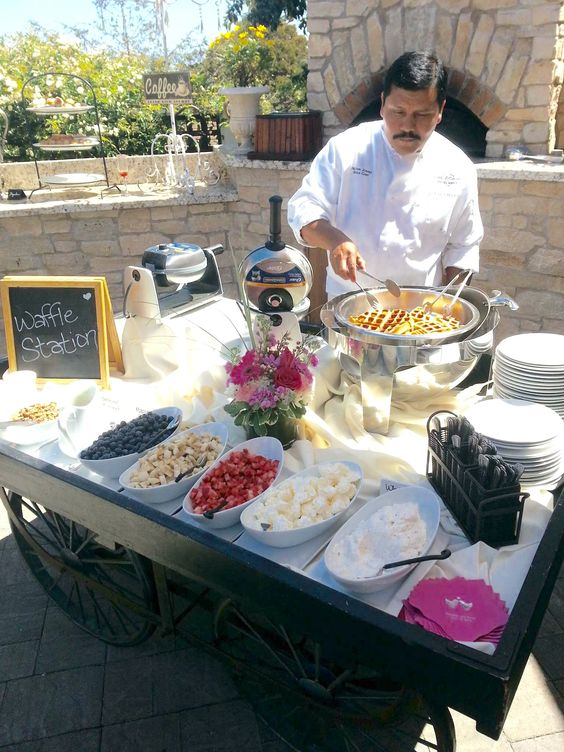 a waffle station on a large cart, with fresh waffles, toppings, sauces, syrups and lots of plates