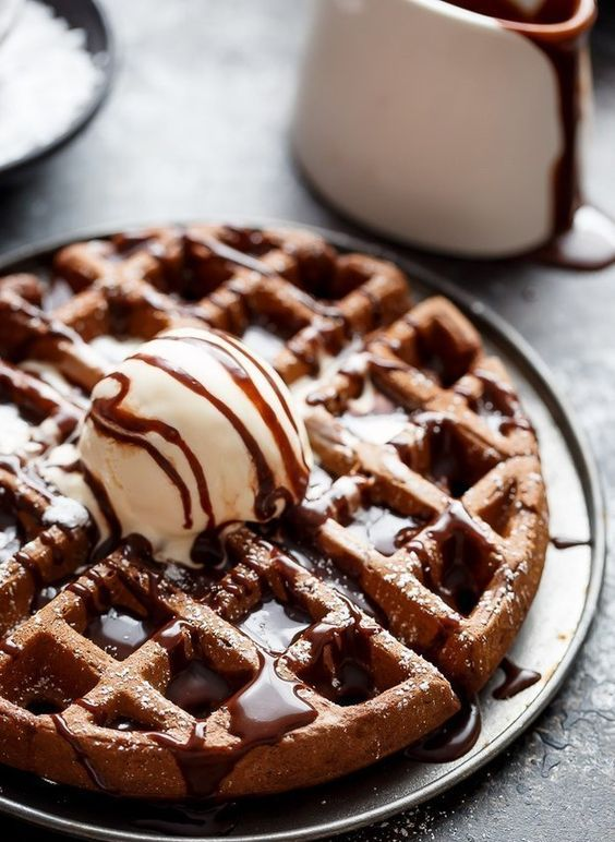 a dark chocolate cake waffle topped with vanilla ice cream and chocolate sauce on top