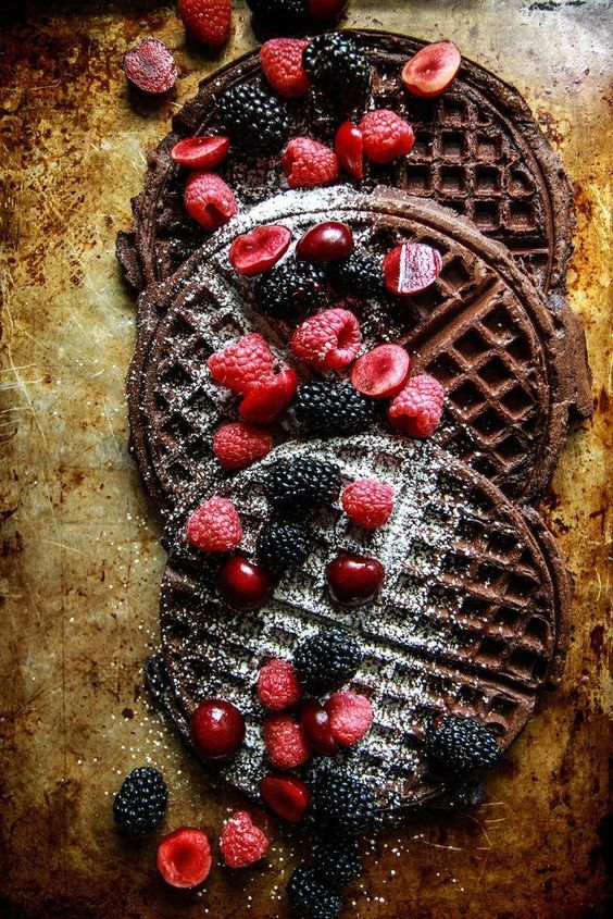 chocolate waffles with sugar powder, rapsberries, cherries and blackberries are delicious