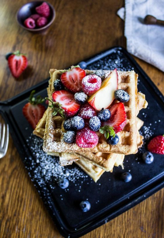 waffles stacked and topped with blueberries, raspberries and strawberries and sugar powder are amazing