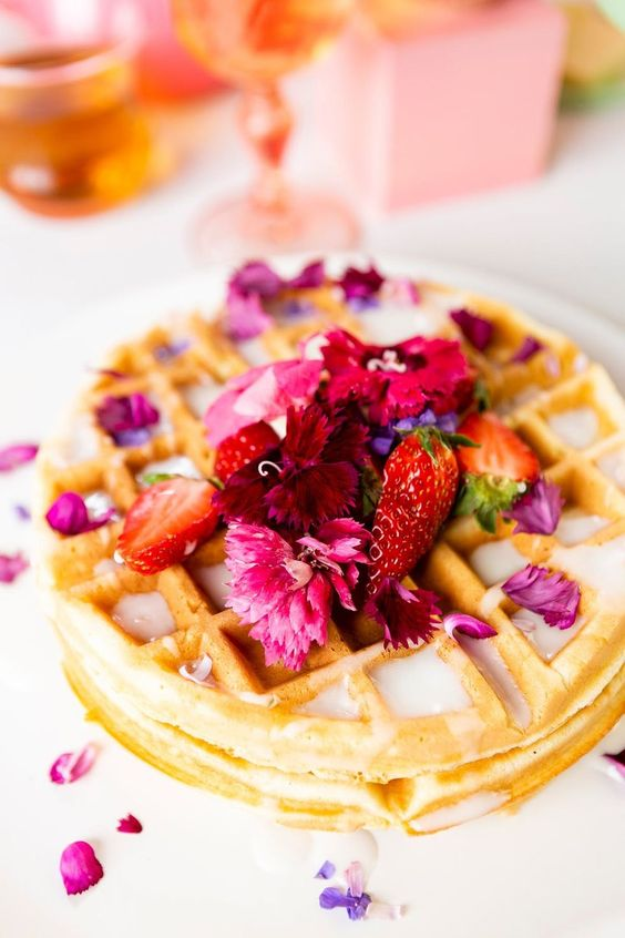waffles topped with bright blooms and strawberries plus creamy sauce are delicious
