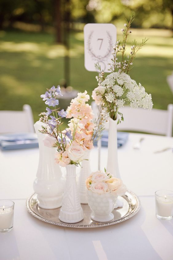 a French country cluster wedding centerpiece of white vases and mugs, pastel and white blooms and a table number
