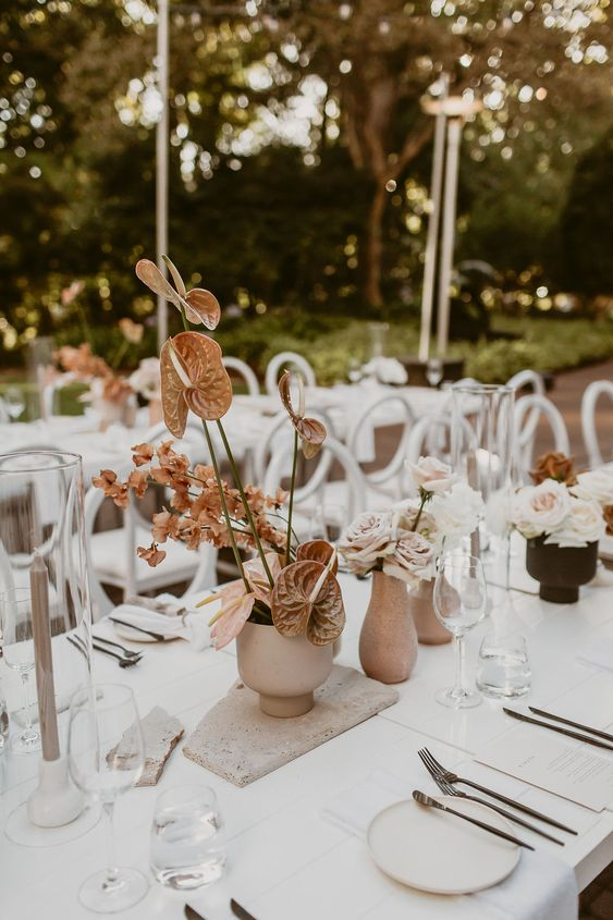 a beautiful and romantic cluster wedding centerpiece with matte vases, blush and rust-colored blooms