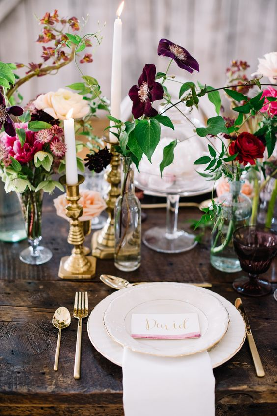 a bright and catchy cluster wedding centerpiece of bottles, glasses and blooms in various shades of pink and burgundy