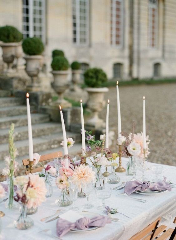 a chic cluster wedding centerpiece of sheer glass vases and bottles, with pastel blooms and tall thin candles